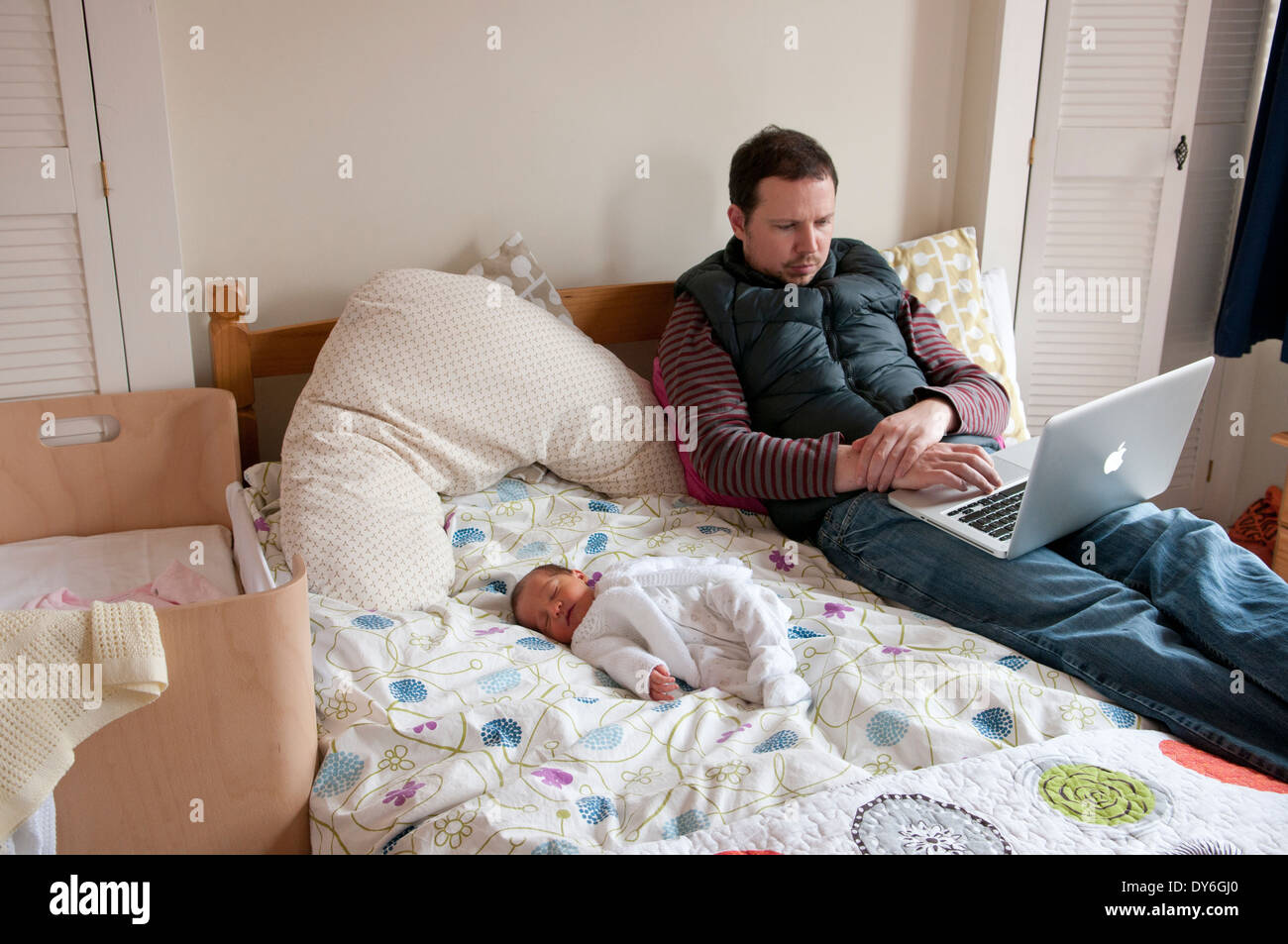 Father with his newborn baby on a bed looking worried - Stock Image
