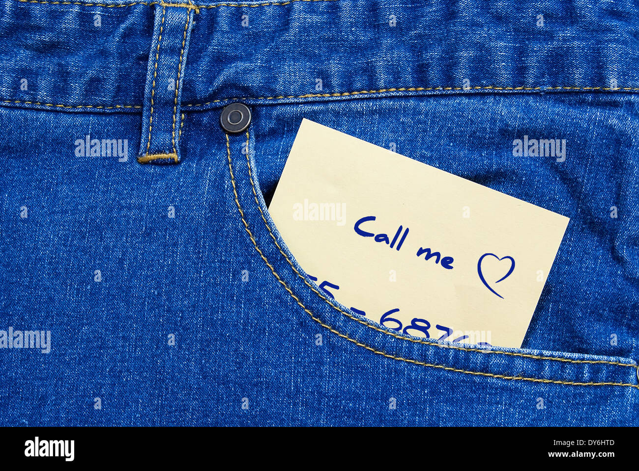 phone number written on a yellow posit a jeans pocket - Stock Image