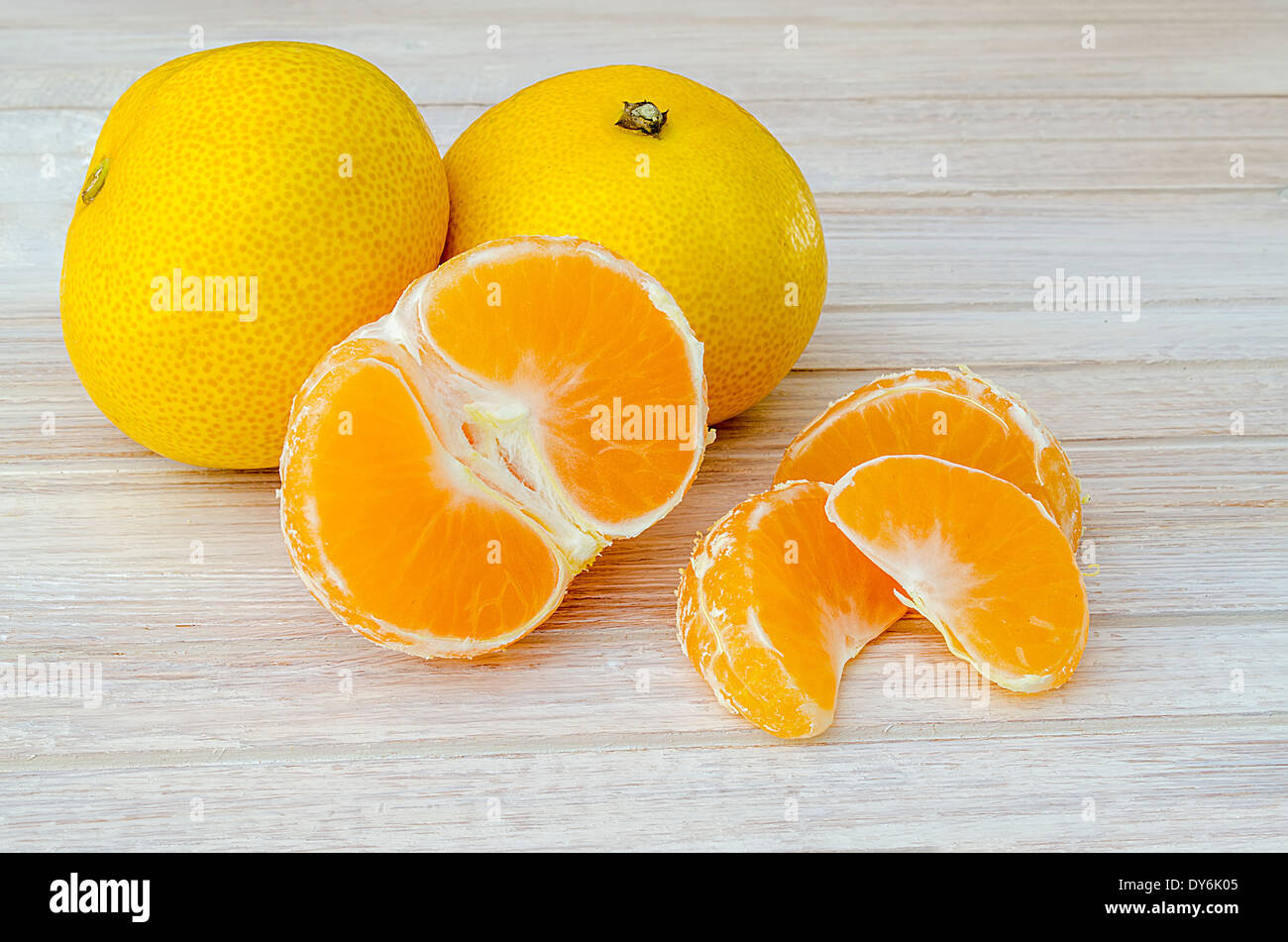 group of tangerines, one peeled and separated into segments on the white kitchen table - Stock Image