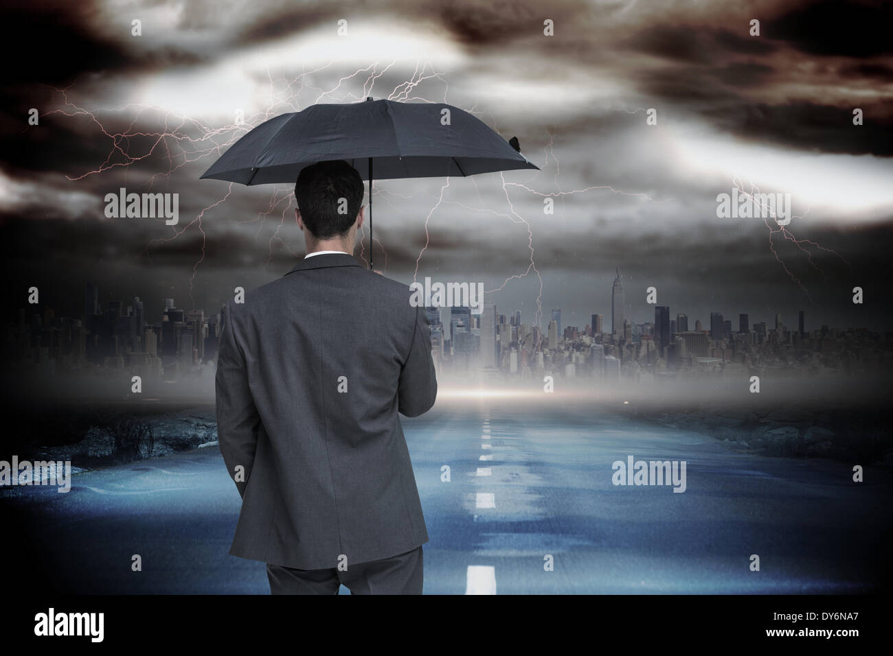 Composite image of rear view of classy businessman holding grey umbrella - Stock Image