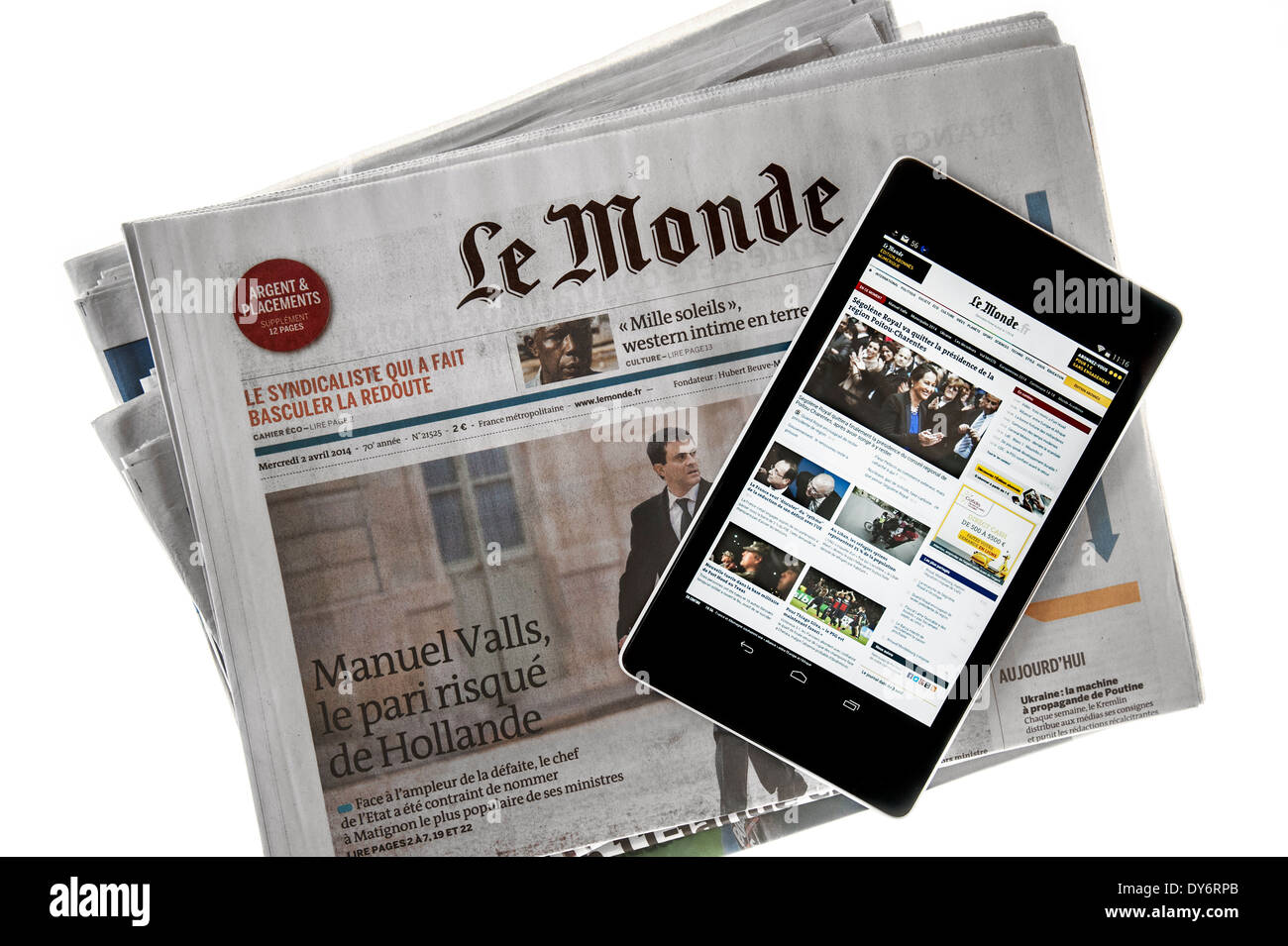 Touchscreen digital tablet showing online world news on top of French Le Monde newspaper on white background - Stock Image