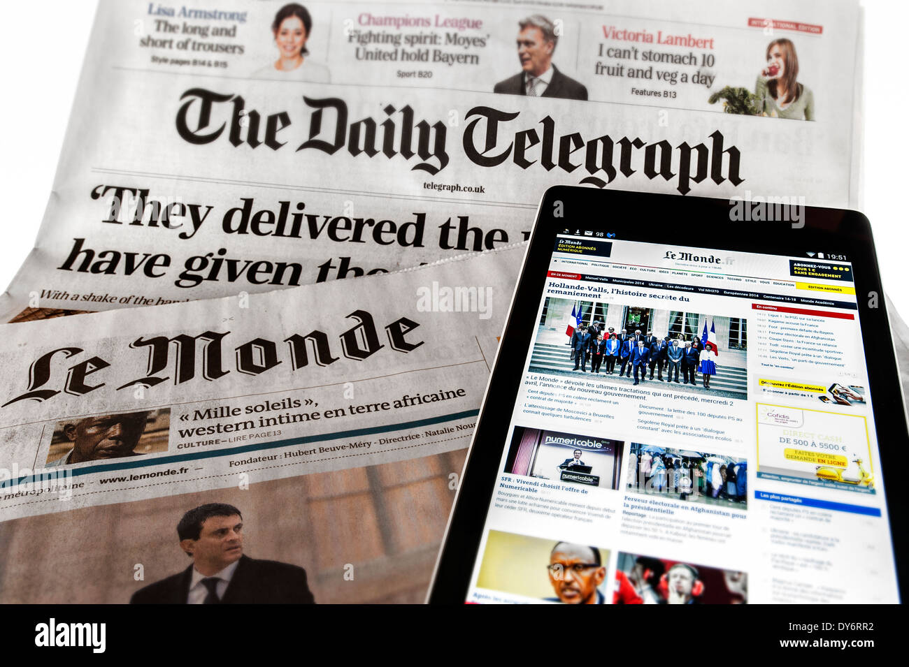 Tablet with  online international news on top of British The Daily Telegraph and French Le Monde newspapers on white background - Stock Image