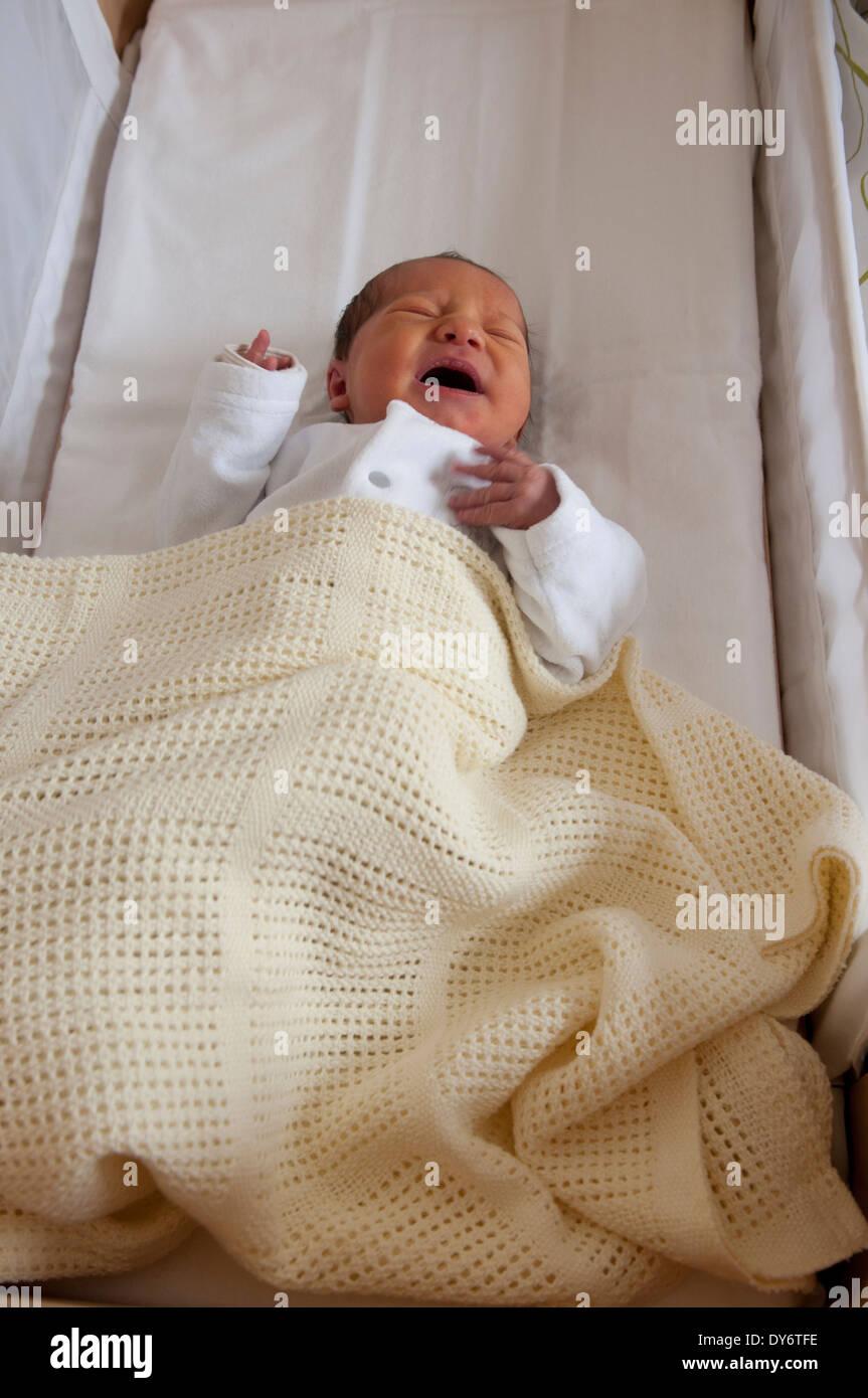 Newborn baby girl lying in her crib crying stock image