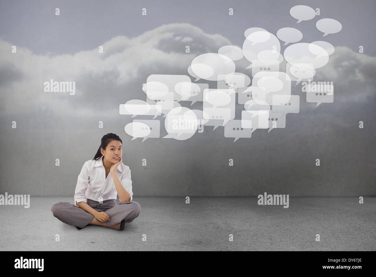 Composite image of businesswoman sitting cross legged thinking - Stock Image