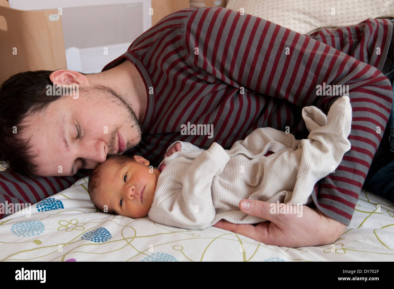Father lying down with his newborn baby girl cuddling - Stock Image