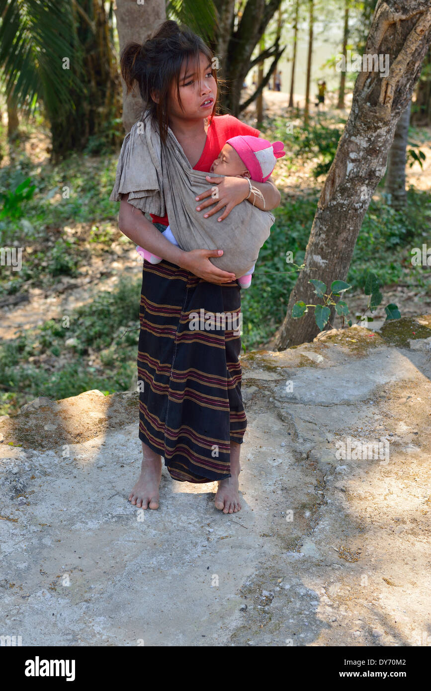 Hmong tribe child carrying a baby in a sling in a village on the Mekong Riverbank in Laos, Lao - Stock Image