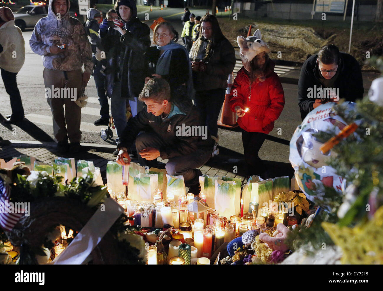 Mourners attend a candlelight vigil at a sidewalk memorial for the