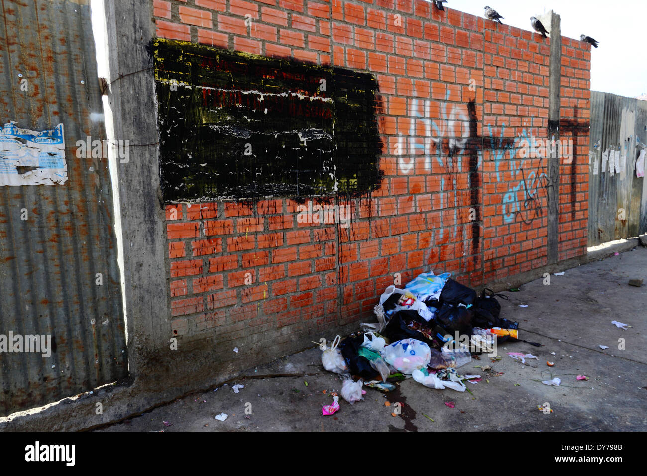 Rubbish dumped on street. Writing on wall telling people not to dump rubbish has been painted over, La Paz, Bolivia - Stock Image
