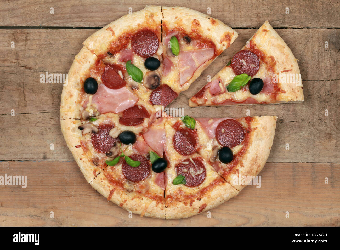 Sliced Deluxe Pizza with cheese, ham, pepperoni, mushrooms and olives on a wooden table - Stock Image