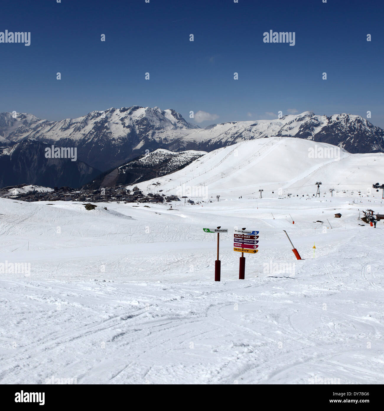 Signs and a snow covered Alpine skiing piste at Alpe d'Huez, France. - Stock Image