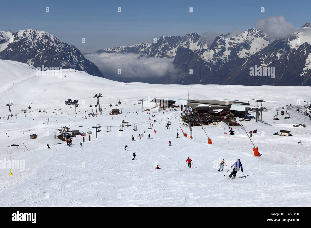 People skiing on a snow covered Alpine piste at Alpe d'Huez, France. - Stock Image