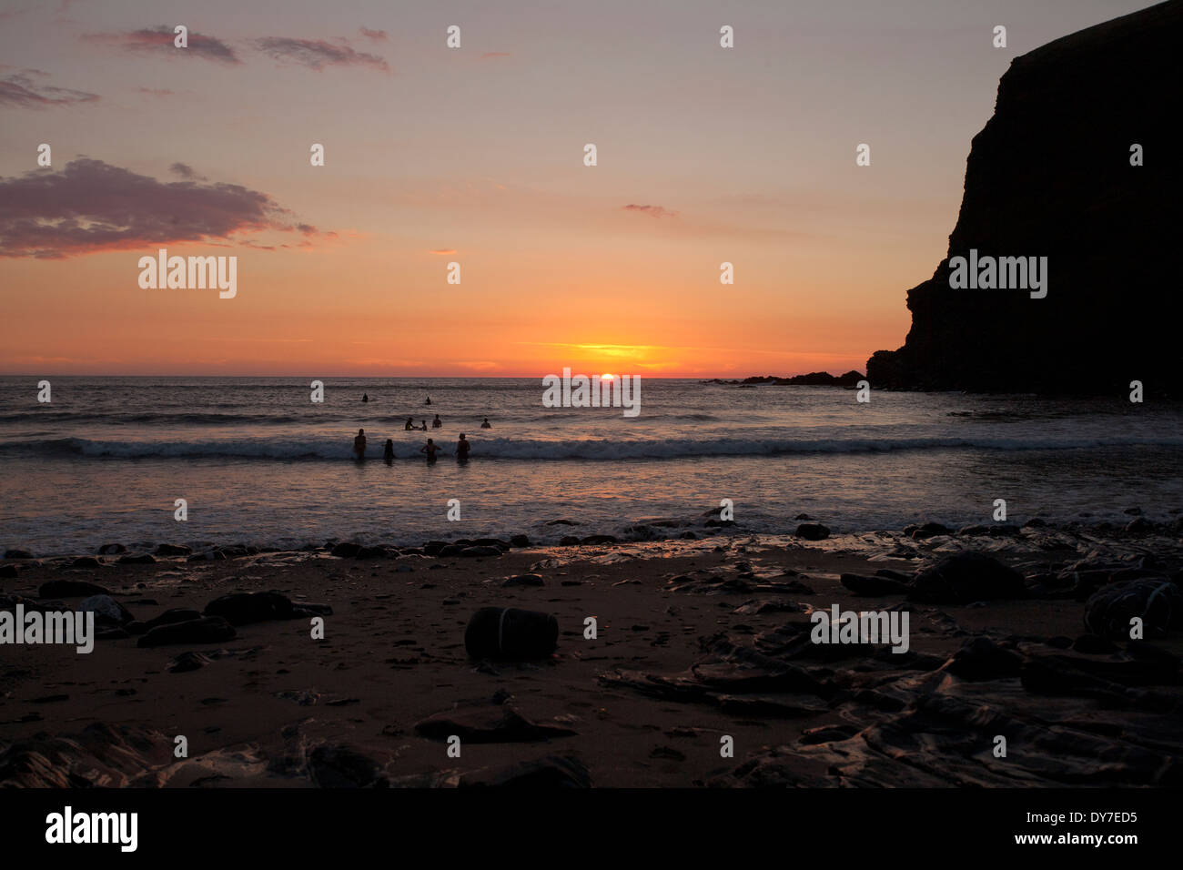 Swimmers and surfers out at sunset in the sea at Crackington Haven - Stock Image