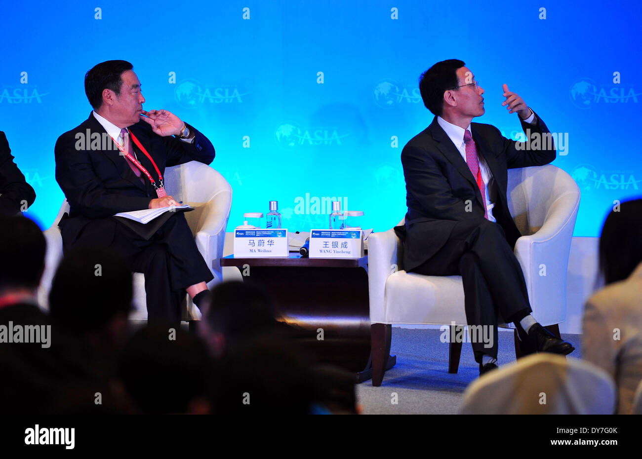 Boao, China's Hainan Province. 9th Apr, 2014. Ma Weihua (L), chairman of Wing Lung Bank Ltd. and former executive director, president and CEO of China Merchants Bank, and Wang Yincheng, vice chairman and president of the People's Insurance Company (Group) of China Ltd., attend a panel of 'Internet-Finance: Towards Rational Exuberance' during the Boao Forum for Asia (BFA) annual conference 2014 in Boao, south China's Hainan Province, April 9, 2014. © Guo Cheng/Xinhua/Alamy Live News - Stock Image
