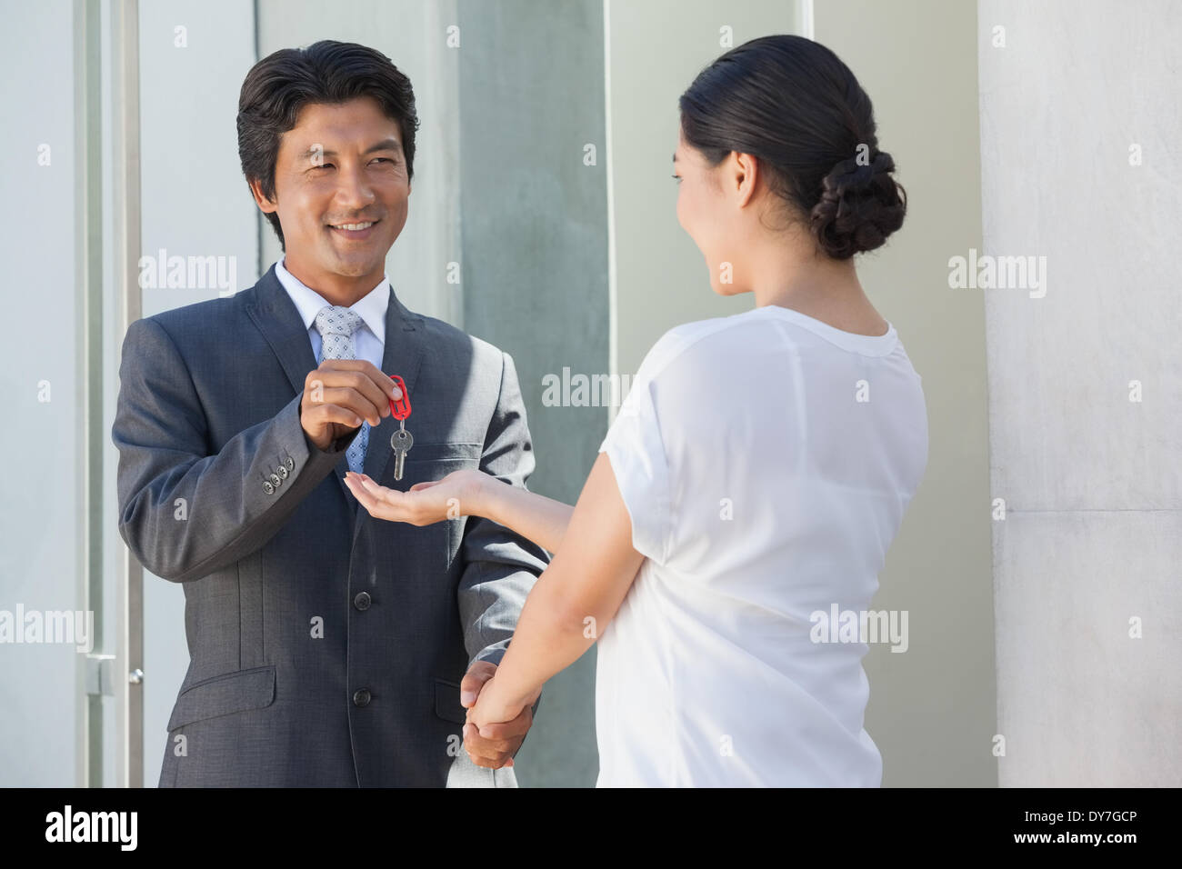 Smiling estate agent giving the key to buyer - Stock Image