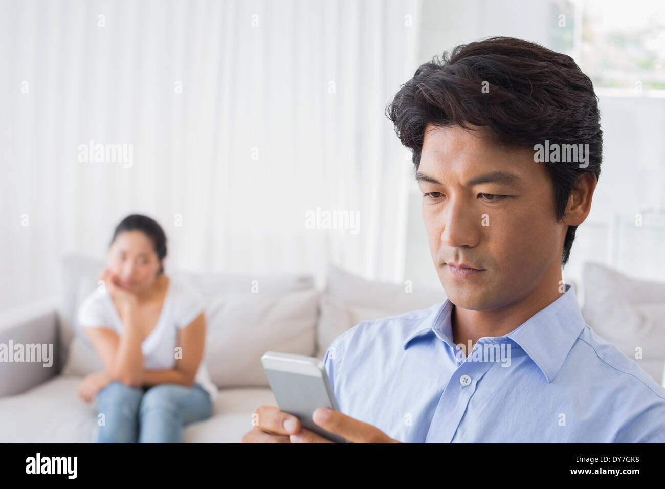 Man sending a text while girlfriend watches from couch - Stock Image