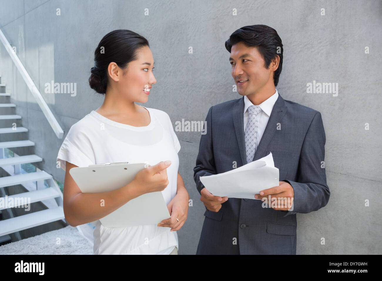 Estate agent showing lease to customer and smiling - Stock Image