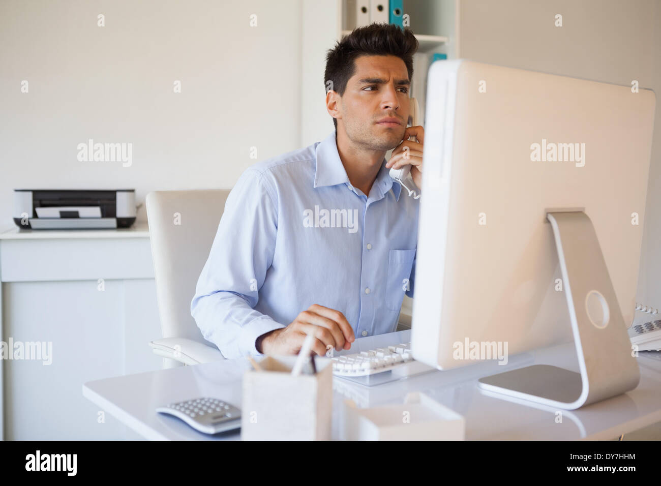 Casual businessman on the telephone at desk - Stock Image