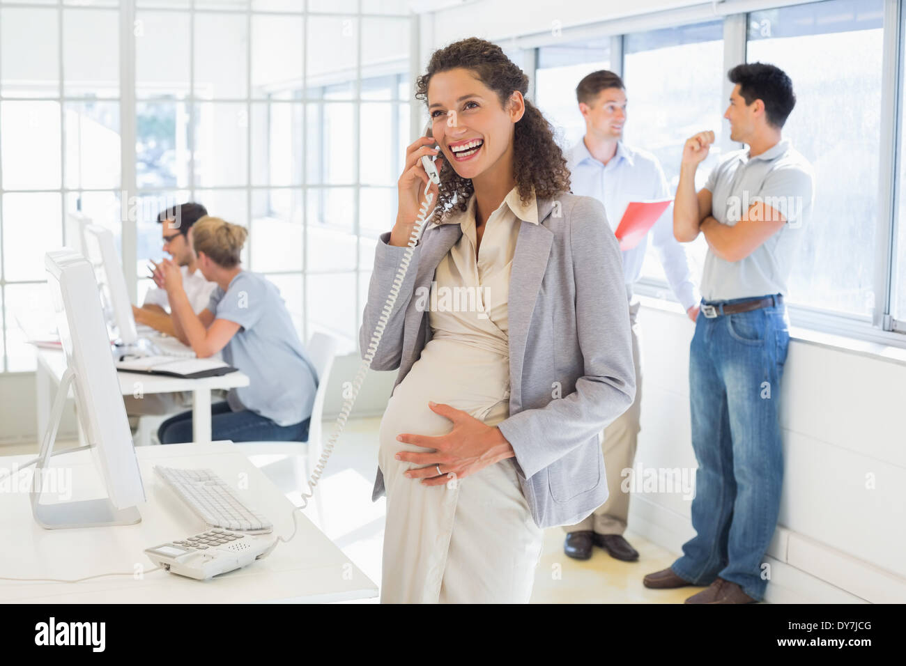 Pregnant businesswoman talking on phone with team behind her Stock Photo