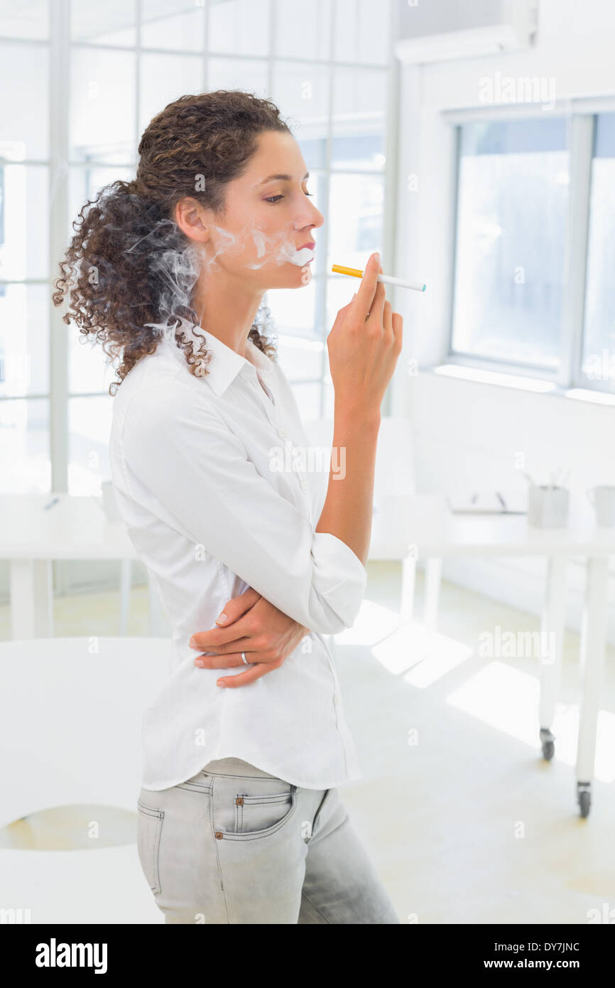 Casual businesswoman smoking an electronic cigarette - Stock Image