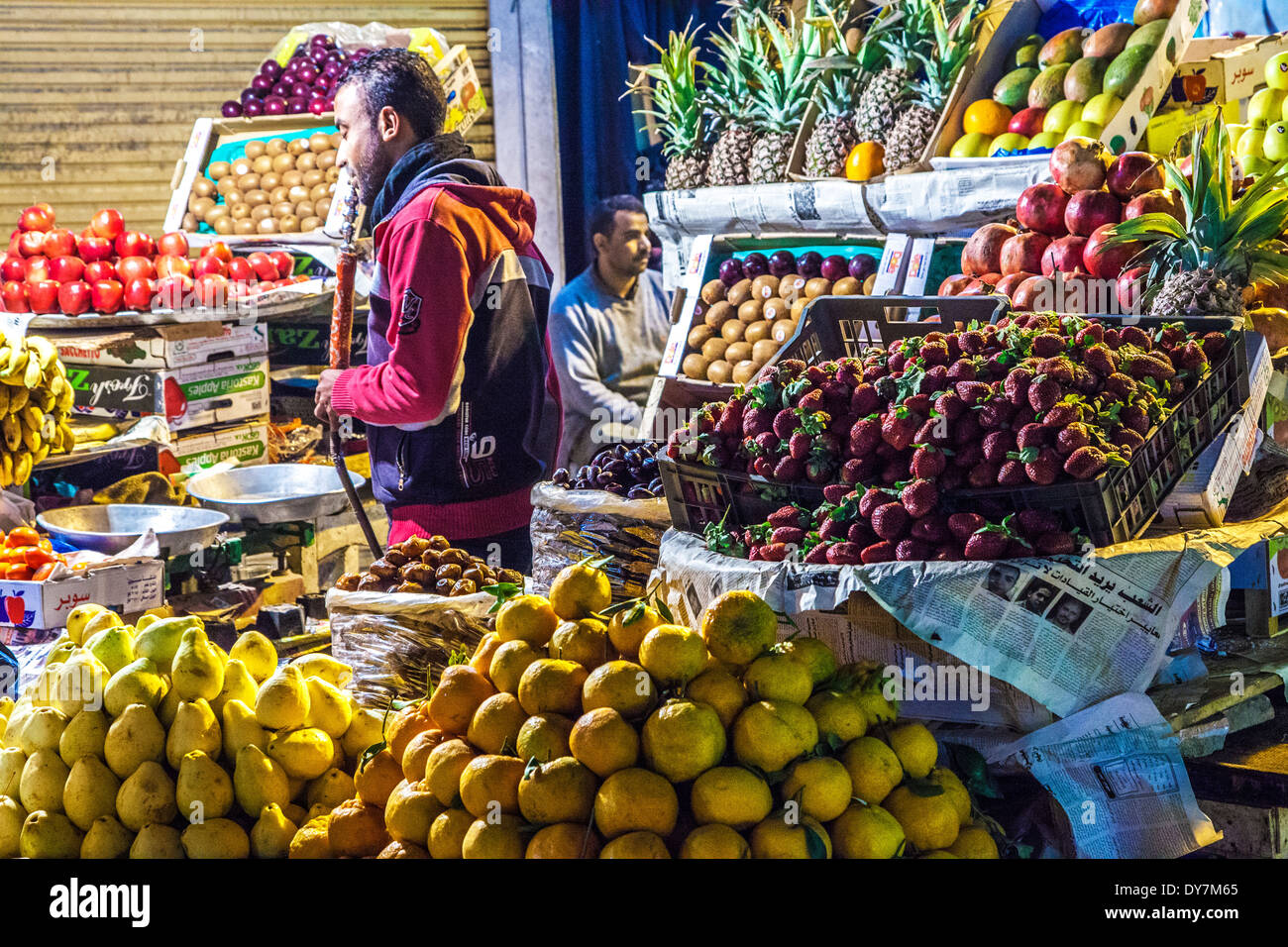 Stallkeeper smoking a hookah behind a fruit stall at the night market or souk in Luxor, Egypt - Stock Image