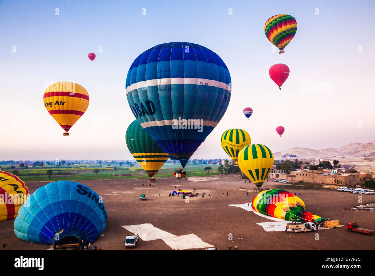 Hot air balloons being inflated and taking off for a sunrise flight from the West Bank of the Nile in Egypt. Stock Photo