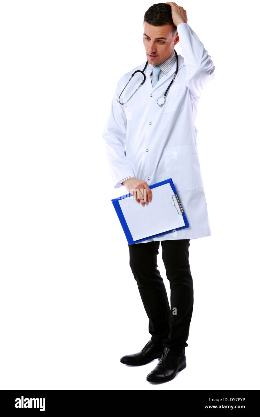 Thoughtful male doctor with clipboard and stethoscope standing over a white background - Stock Image