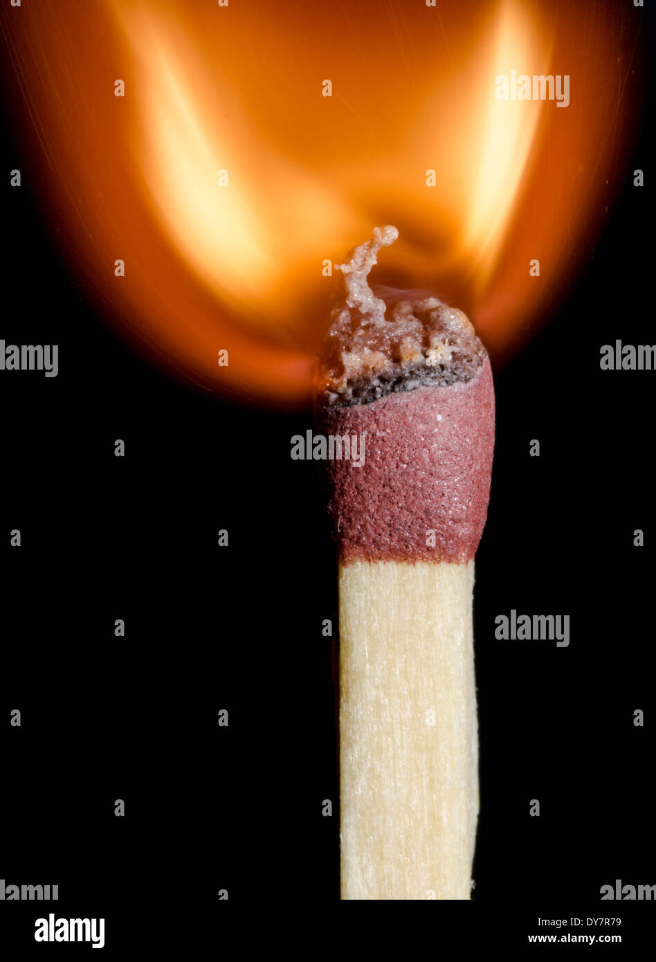 A match just as it is igniting, on a black background. - Stock Image