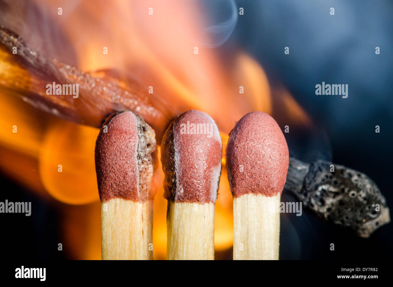 Lighting matches. 3 matches being lit from behind by another match, on a black background. - Stock Image