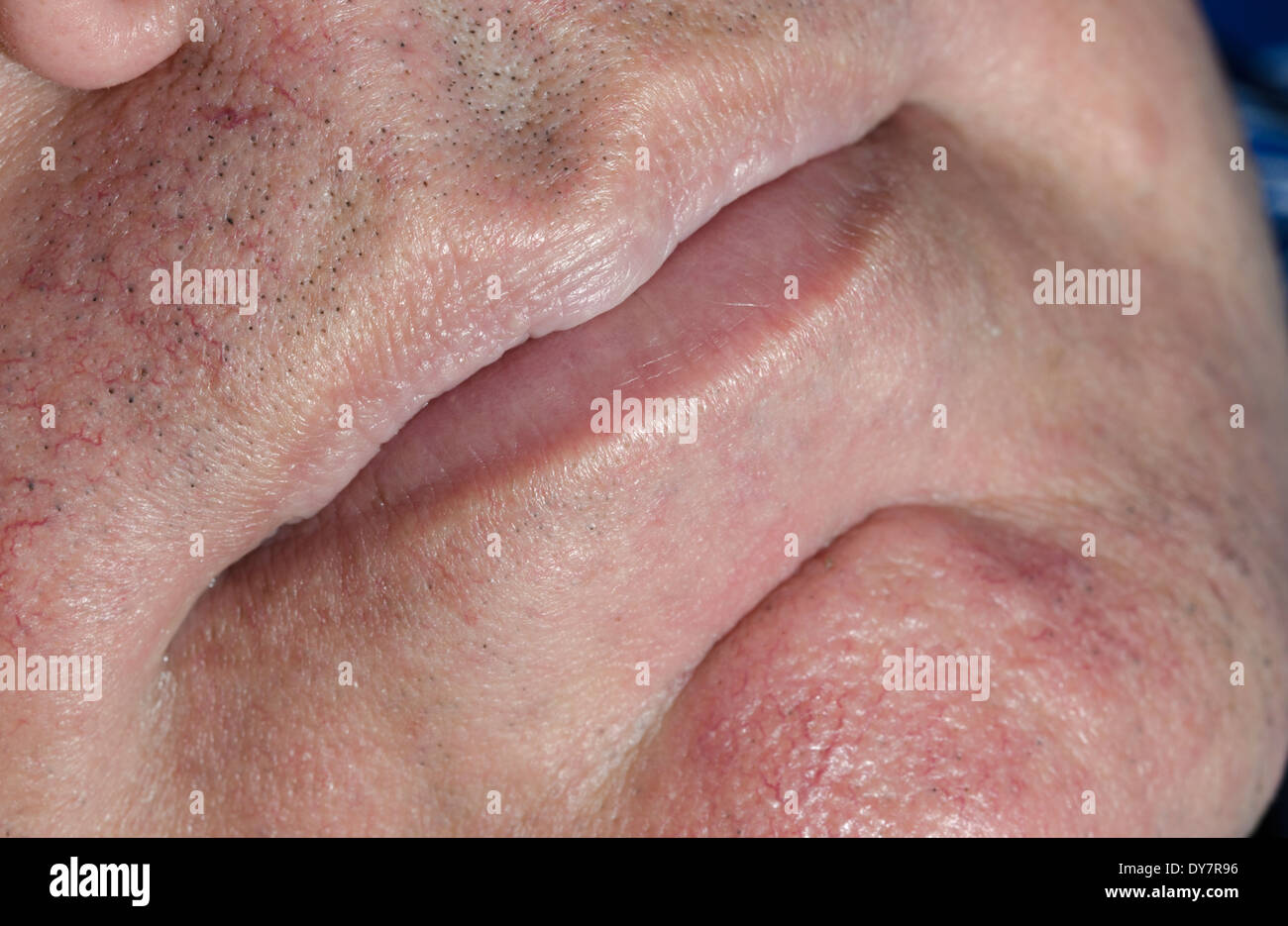 Mouth and lips closeup on a white mans face. - Stock Image