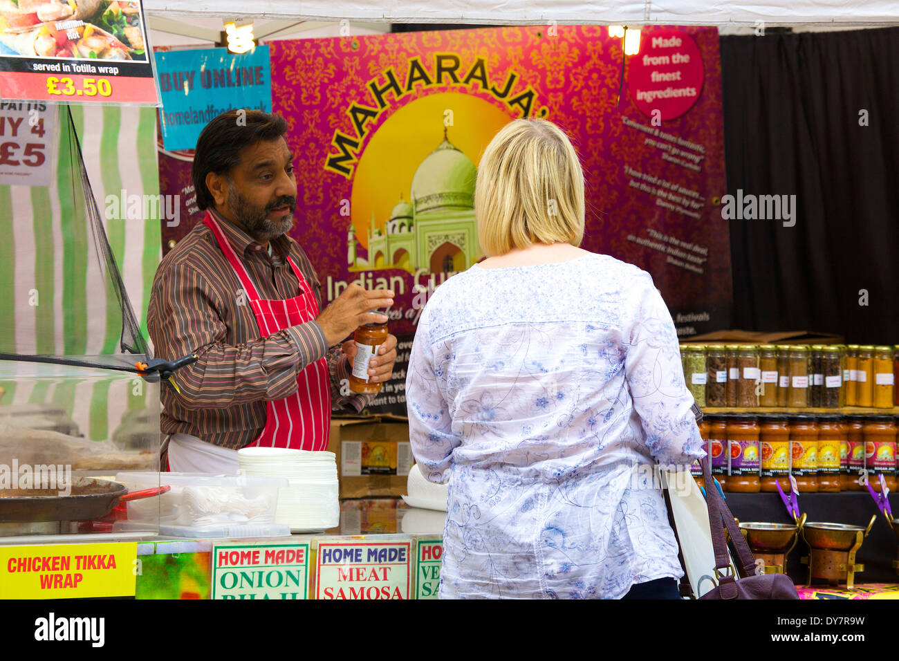 Woman in front of Indian food stall at food festival. Carlisle Continental Market, Carlisle, Cumbria, England, United Kingdom. - Stock Image