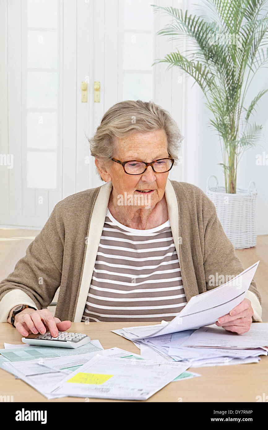 Elderly person doing paperwork - Stock Image