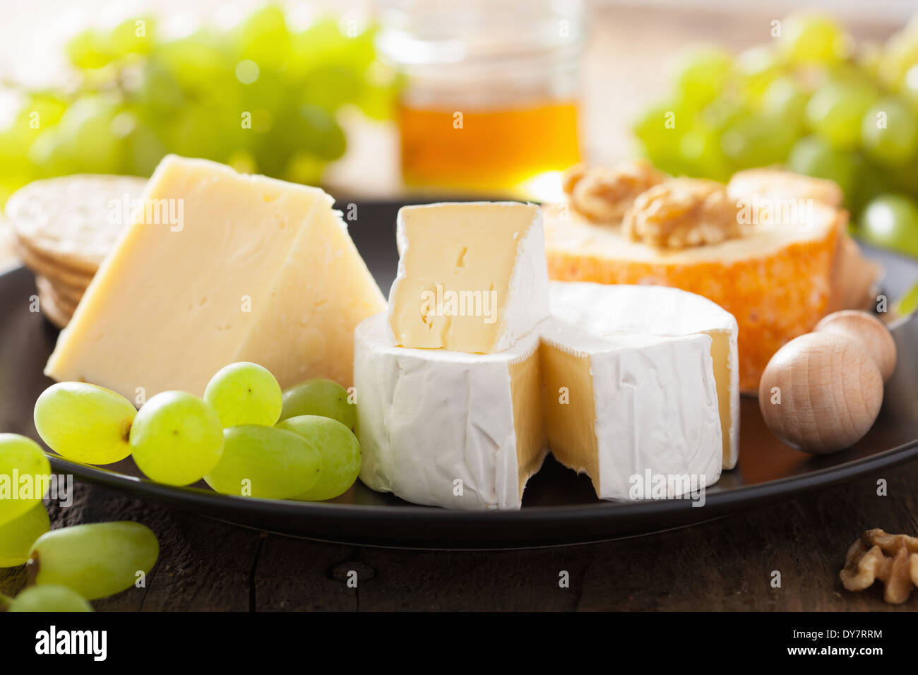 various types of cheese with grapes, honey and nuts - Stock Image