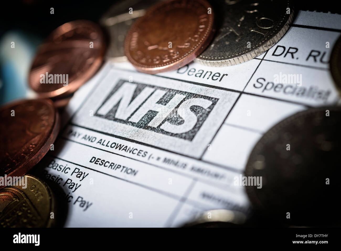 NHS Salaries and Wages concept - A Doctor's NHS Payslip with British coins - National Health Service budget cuts - Stock Image