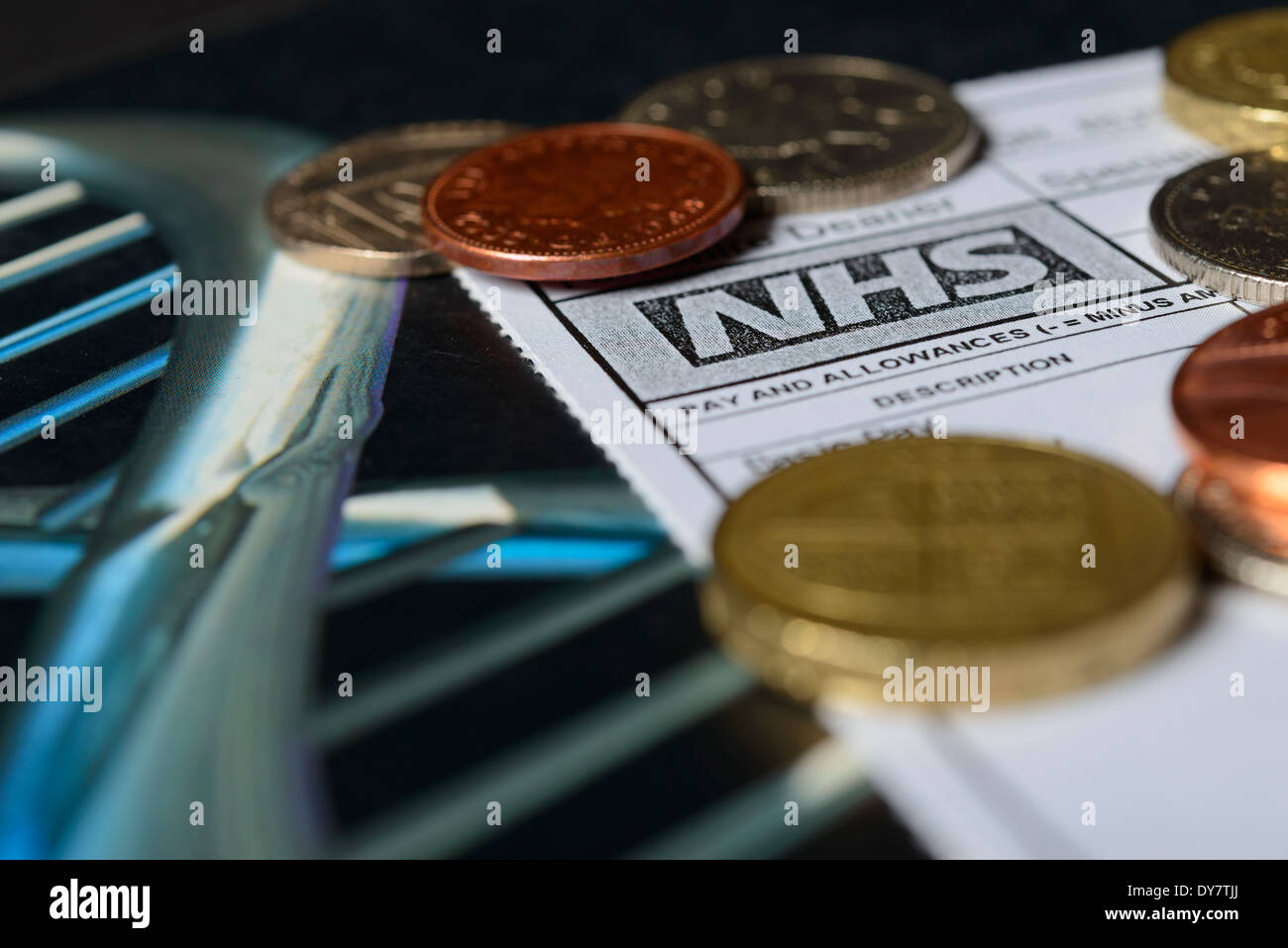 Doctors' Pay - A  Doctor's NHS Payslip with coins on a medical text book. Contract and pay negotiations in the UK concept. - Stock Image