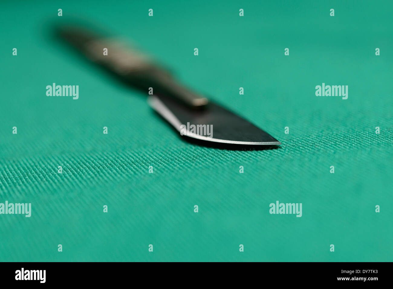 Surgical Instruments - a sharp, two-piece scalpel on green surgical drapes, shot with a shallow depth of field. - Stock Image