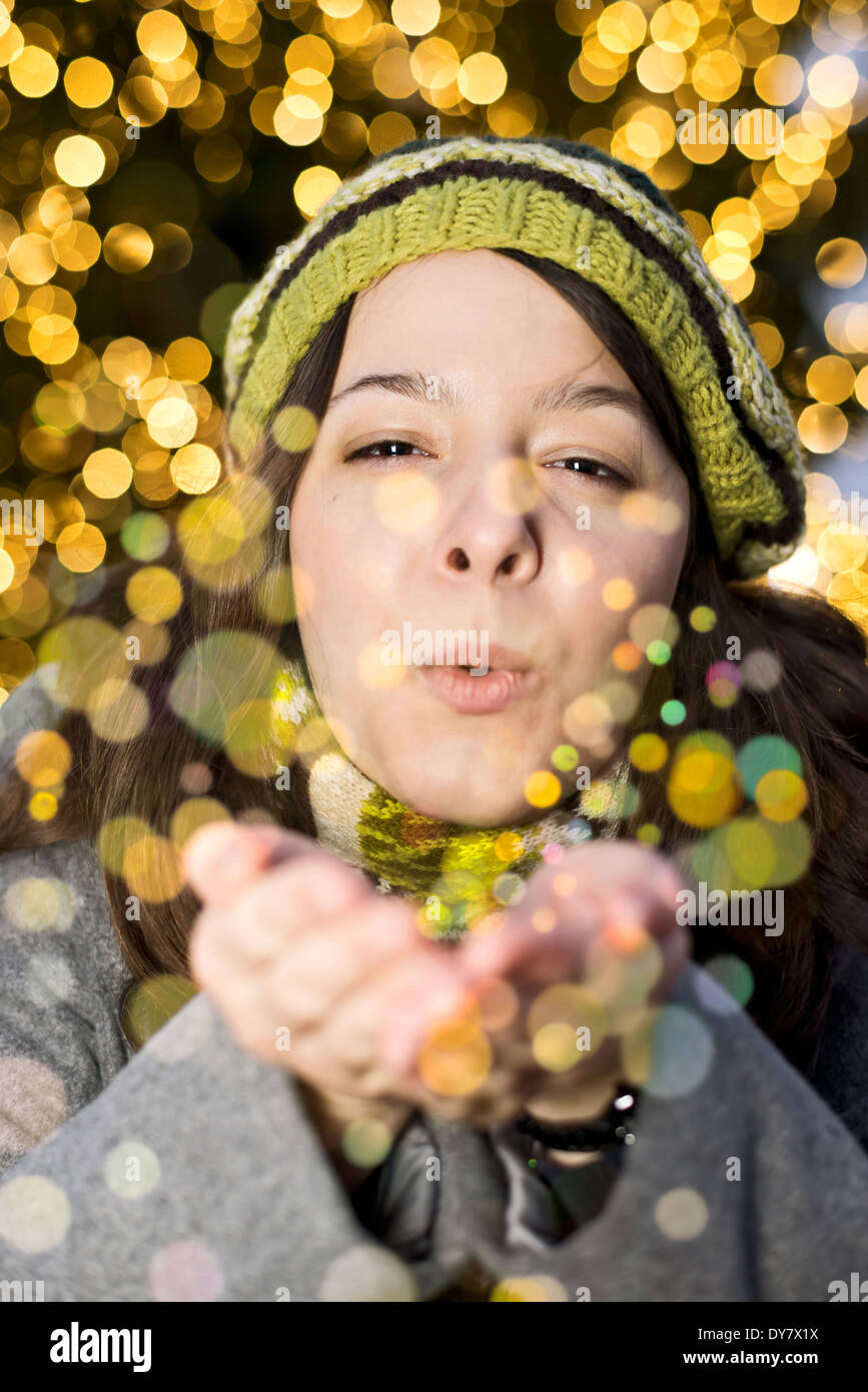 Portrait of young woman blowing golden glitter - Stock Image