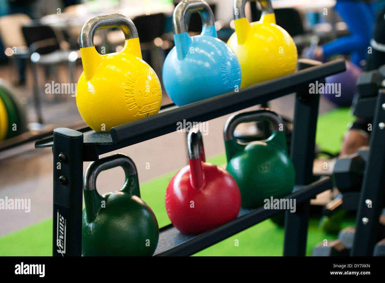 Coloured weights on the fitness fair FIBO in Cologne, Germany. - Stock Image