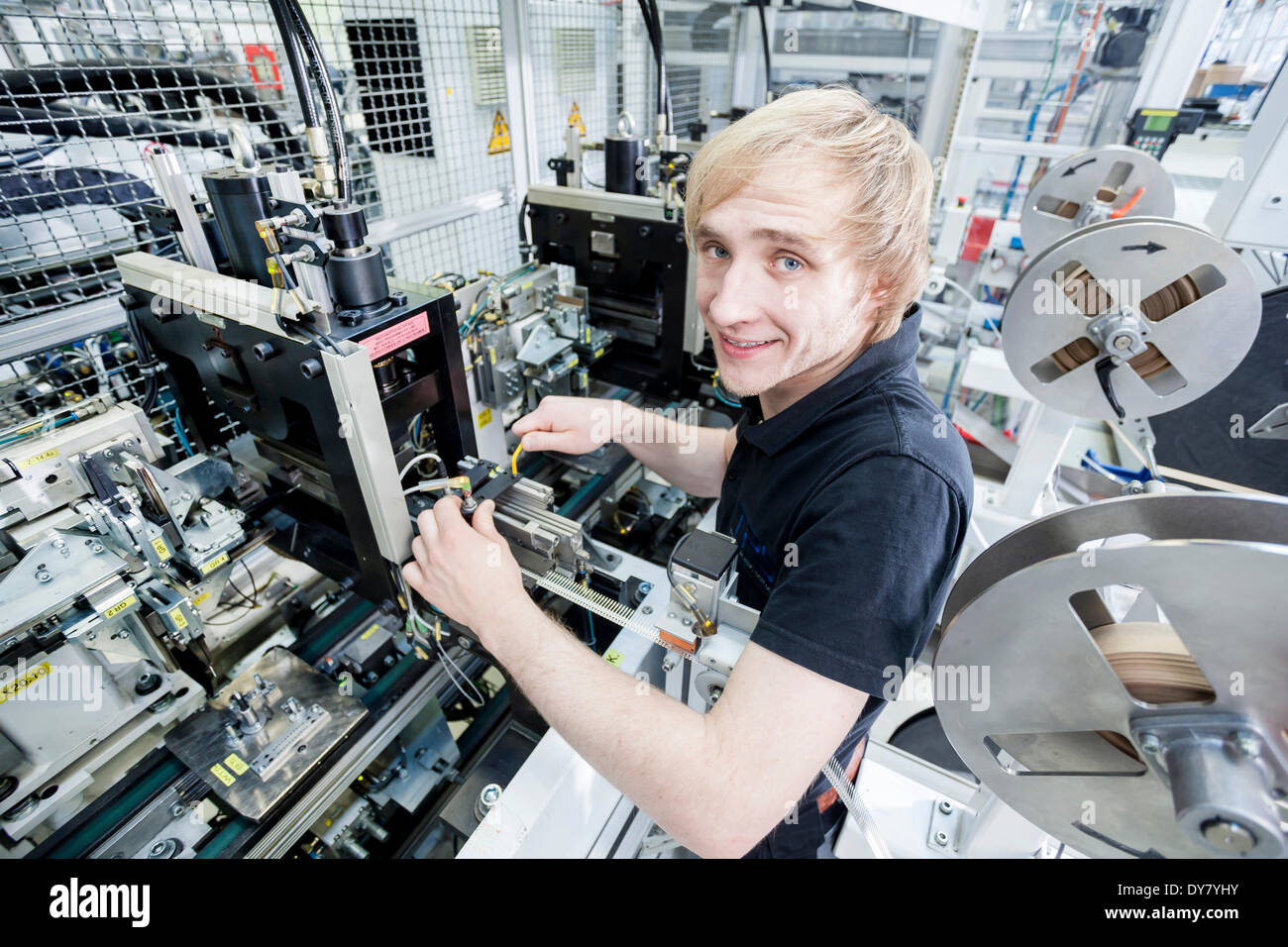 Fabian Kerscher, best trainee nationwide in 2013 in the field of mechatronics, adjusting the sensor position at a punch, - Stock Image