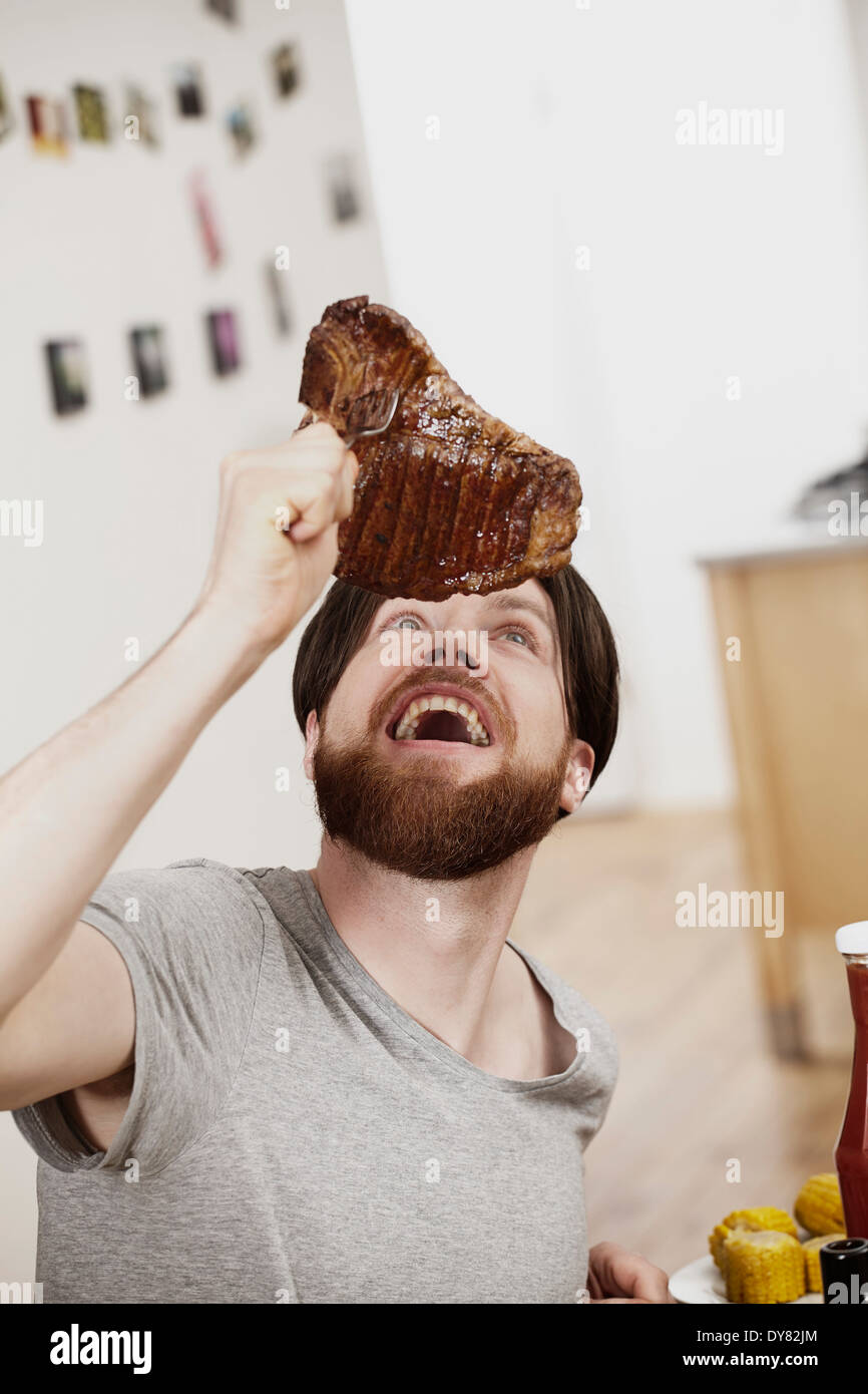 Amazed man looking at large steak - Stock Image