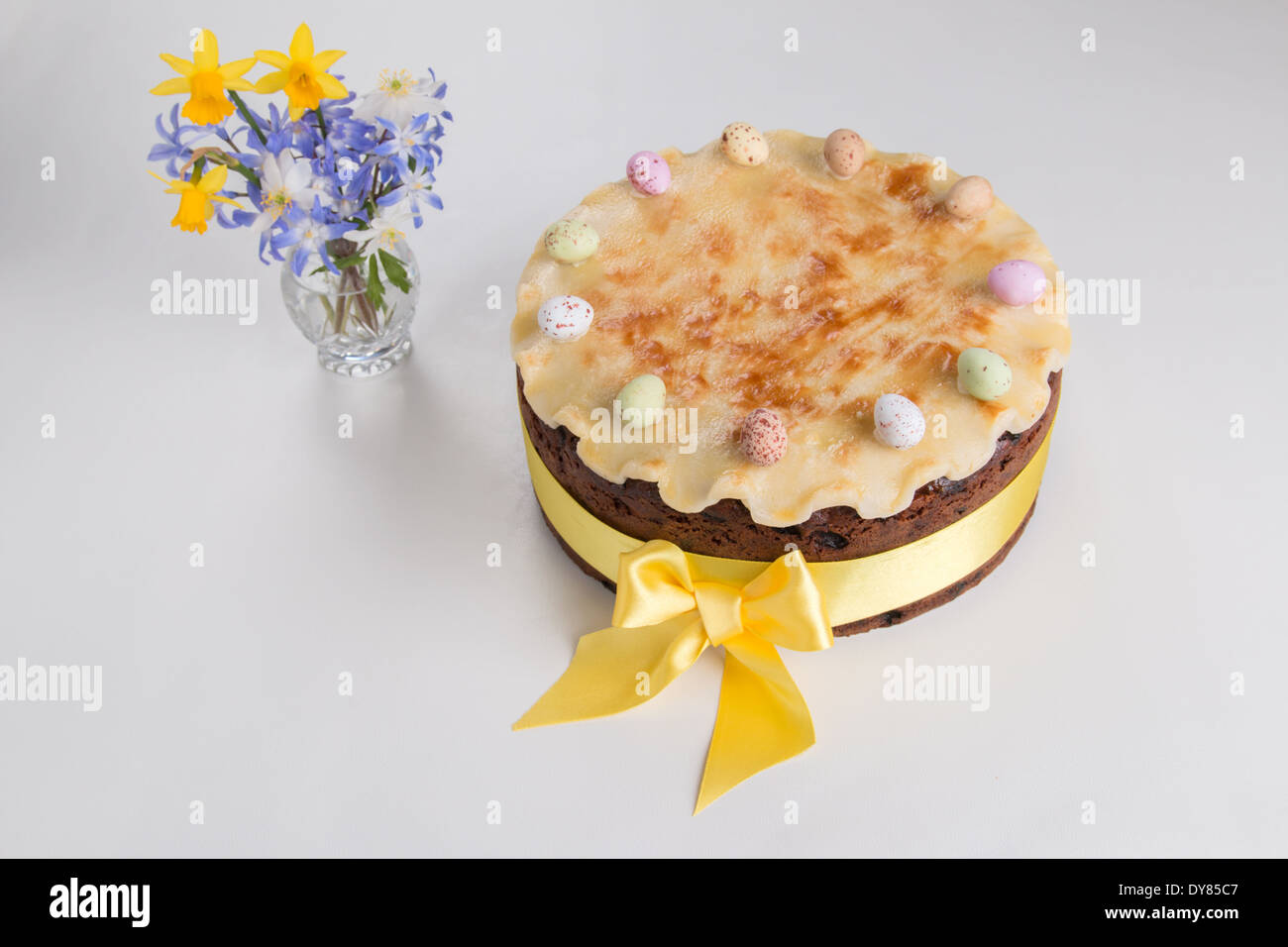 Simnel cake on a light background with fluted marzipan a yellow ribbon with a bow with 11 coloured eggs flowers(30 of 35) - Stock Image