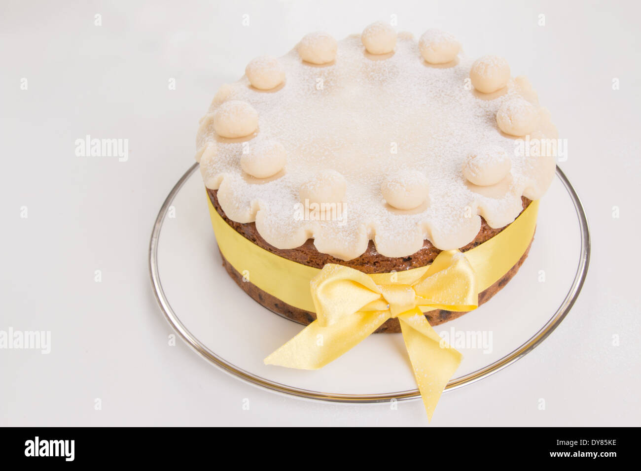 Simnel cake with basic marzipan decoration with a yellow ribbon round it sprinkled with icing sugar/powdered sugar (18 of 35) - Stock Image