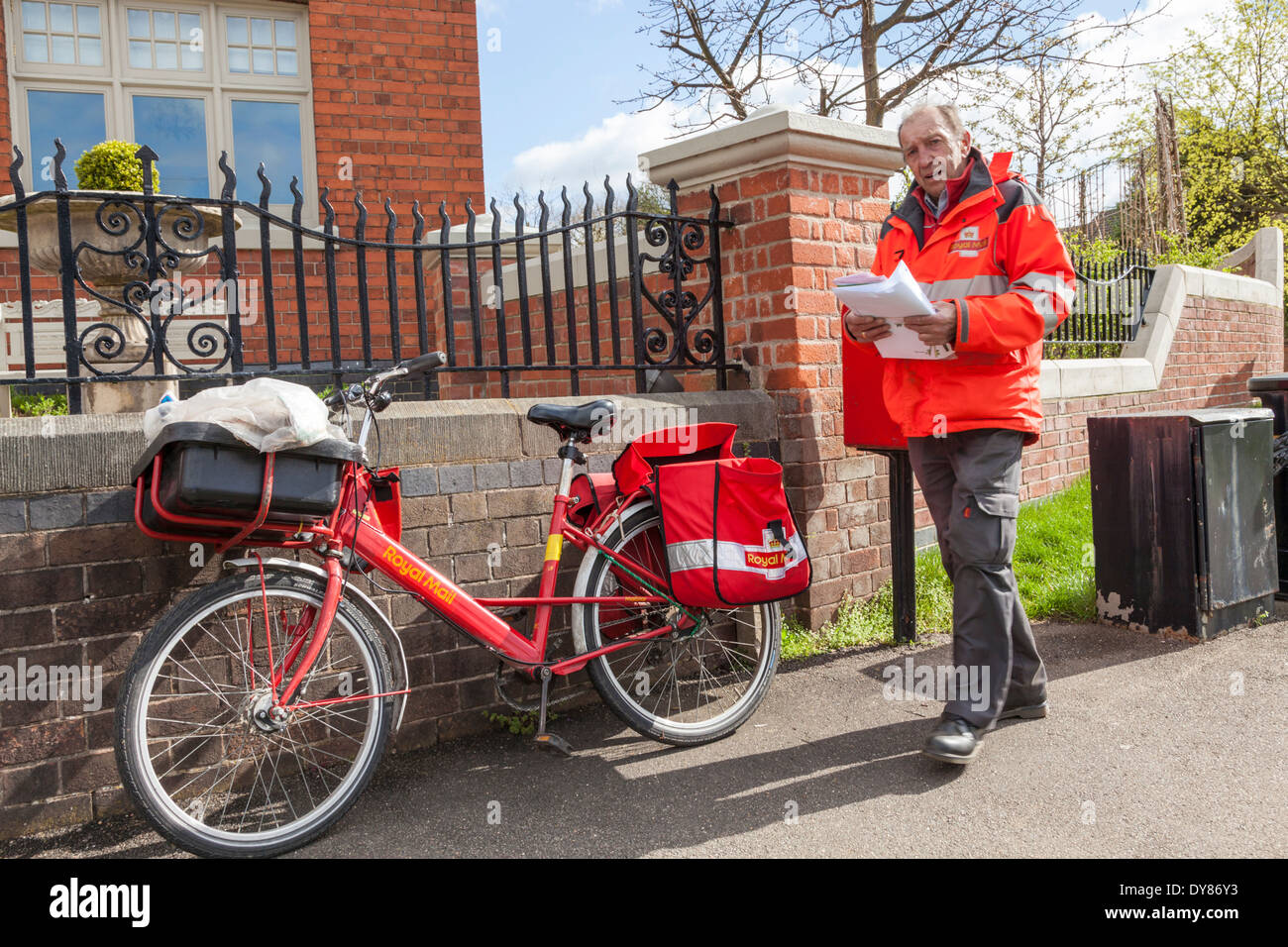 Royal Mail postman with bicycle delivering post in the village of Plumtree, Nottinghamshire, England, UK - Stock Image
