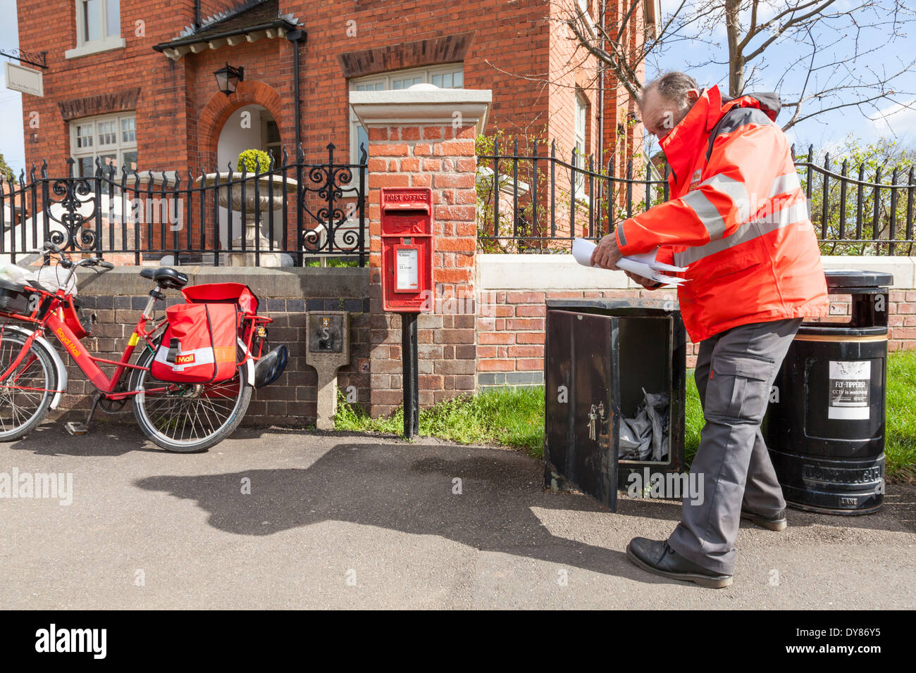 UK postman on his round in a rural area, collecting and delivering mail from a box outside the Old Post Office, Plumtree, Nottinghamshire, England, UK - Stock Image