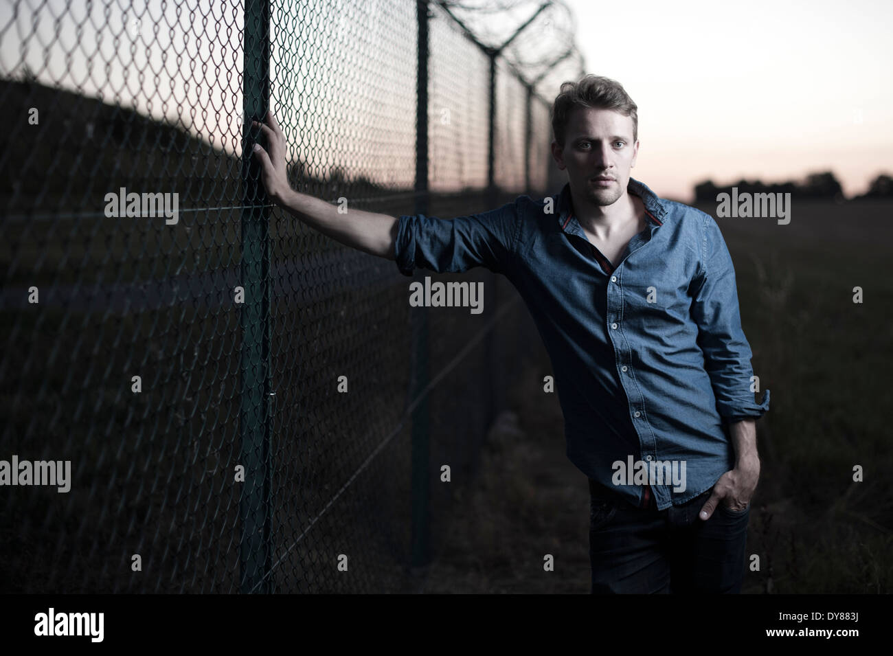 Young man at a chain link fence - Stock Image
