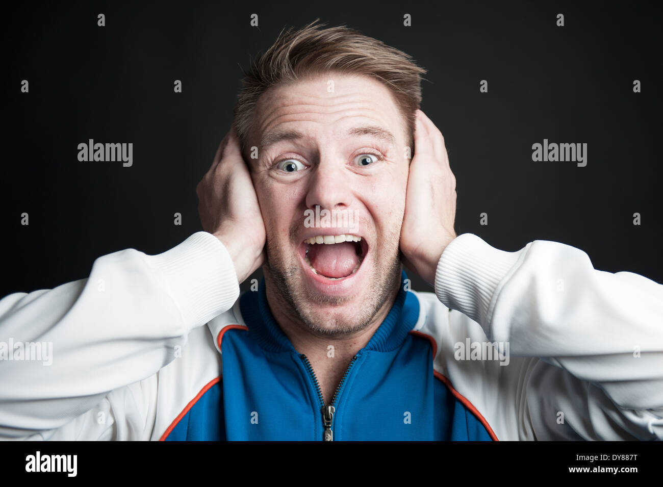 Shocked man holding his ears - Stock Image