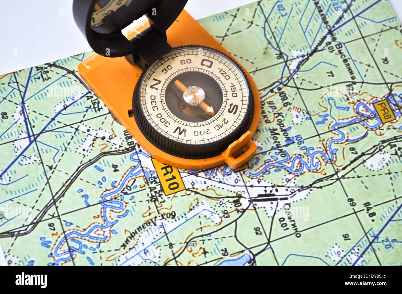 Topographic map lies on a white background and there is a magnetic topographic map lies on a white background and there is a magnetic compass in a black case on an orange ground gumiabroncs Images