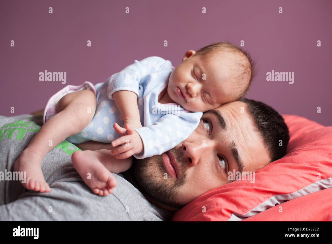 Newborn baby sleeping with father - Stock Image