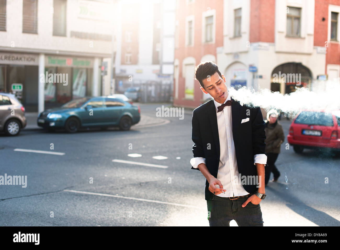 Smoking young man in the city - Stock Image