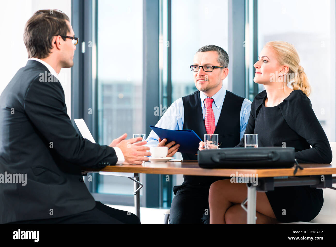 Business - young man in an Job interview, hands over his application papers to the boss and his female assistant in their office - Stock Image