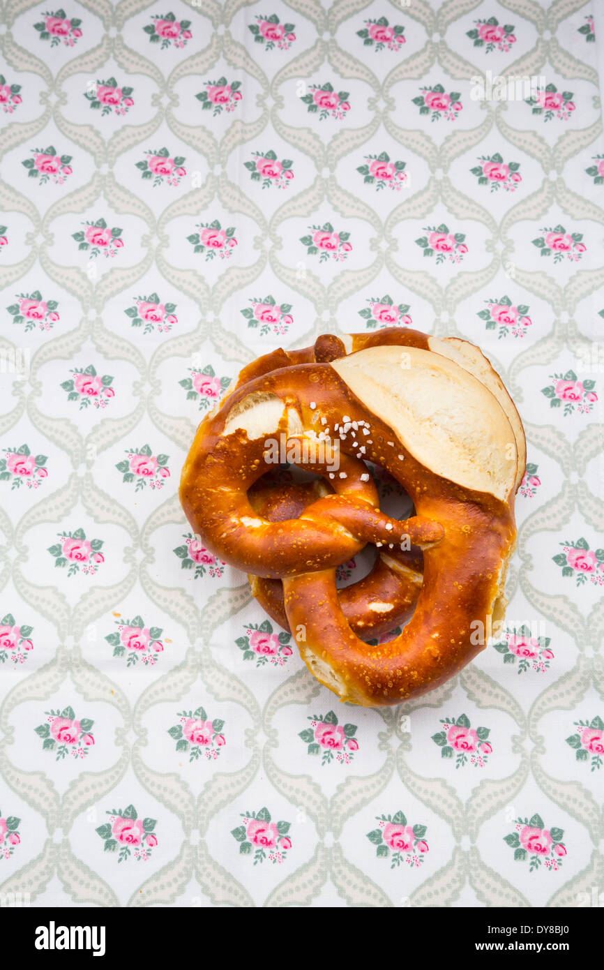 Two salted pretzels on table cloth with  floral pattern - Stock Image